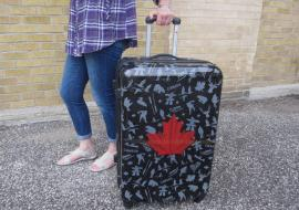 a woman with a suitcase bearing the Canadian maple leaf