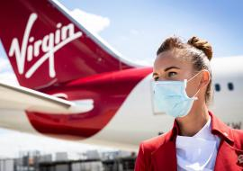 Virgin Atlantic plane tail and flight attendant wearing a face mask